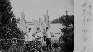 Svågrarna med en kamrat framför segelbåten